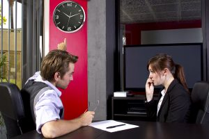Photo of a male office boss angry at a trady female employee. He is talking to her about the time and how late she was. They are talking in a business office with a clock on the wall. The businessman is frustrated and the businesswoman is stressed out.